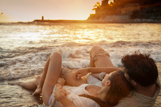 couple laying on sand at beach picture id141338475